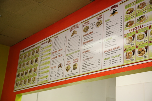 The bright and colorful menu attracts customers into Chuy's Taco Shop. There are many different varieties to choose from.